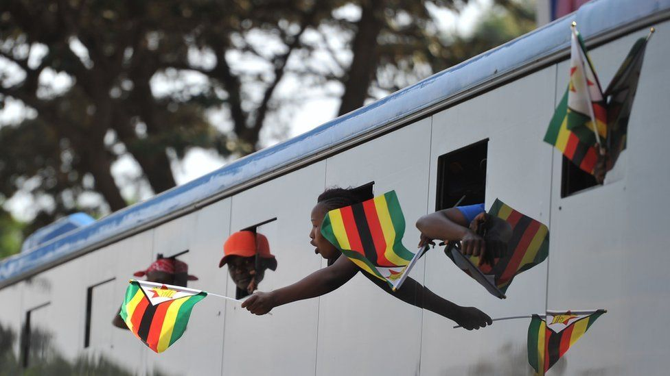 Supporters of Zimbabwe's incoming president wave Zimbabwean flags from a bus as they arrive at Zimbabwe's ruling Zanu-PF party headquarters in Harare on November 22, 2017.