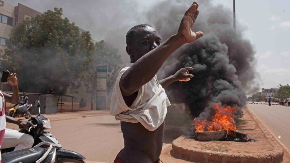A Burkina Faso protestor gestures in front of burning tires as he and others take to the streets in the city of Ouagadougou, Burkina Faso, Thursday, 17 September 2015