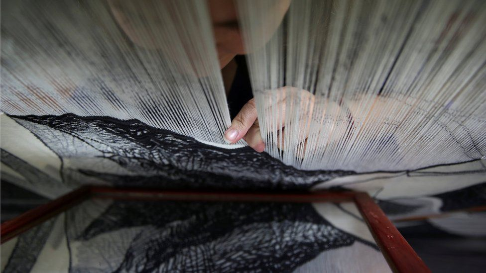 Marta Soria, 34, checks her work on a mirror as she hand-weaves a tapestry on a centuries-old loom at the Royal Tapestry Factory