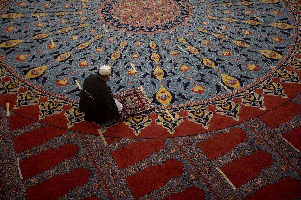A man kneels in prayer inside a mosque.