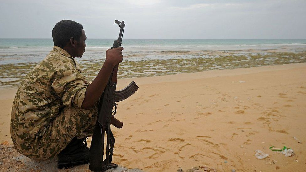 A member of the Somali security forces stands guard on the beach on the coast of Qaw, in Puntland, in 2016.
