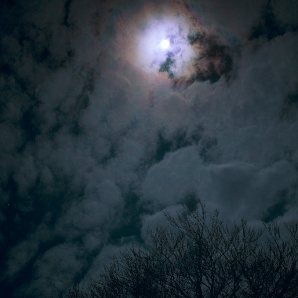 An image of the moon shining through clouds