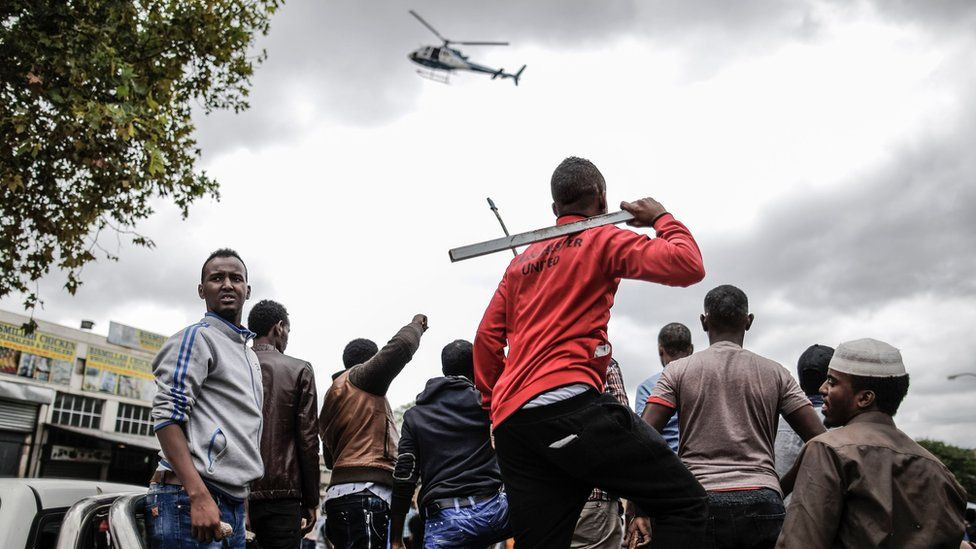Helicopter flies low as group of men, some armed, stand in a crowd