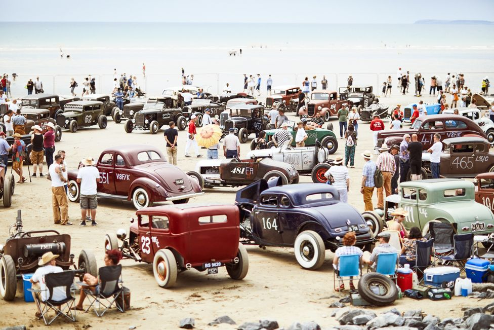People gather on a beach with vintage cars