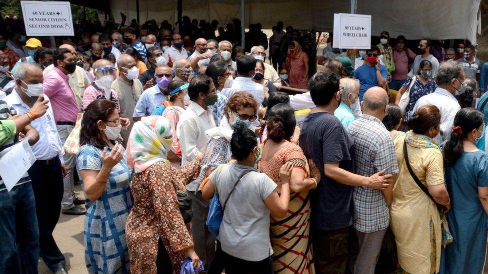 Бенефициары старше 45 лет, ожидающие в длинной очереди на вакцинацию в Центре вакцинации NESCO Jumbo Covid-19 в Горегаоне, 29 апреля 2021 года в Мумбаи, Индия.