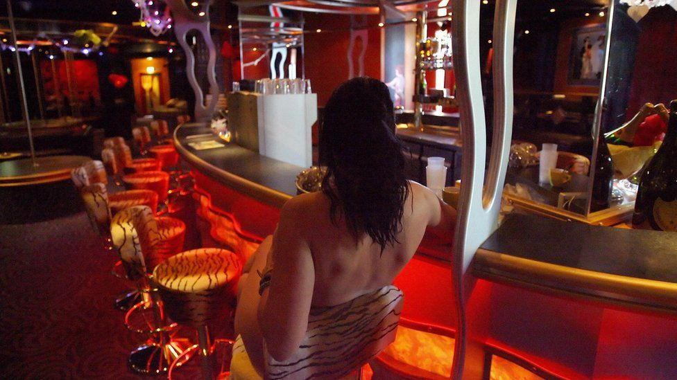 A sex worker poses at the bar of Berlin's Artemis brothel 04 May 2006
