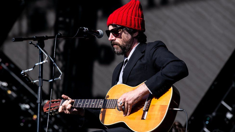 Gruff Rhys on stage in a red bobble hat and suit, playing a guitar
