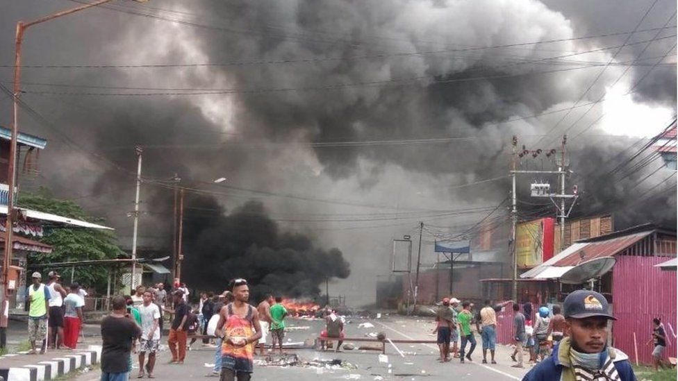 Large clouds of smoke are see amid debris and fire on the streets of Manokwari, Papua