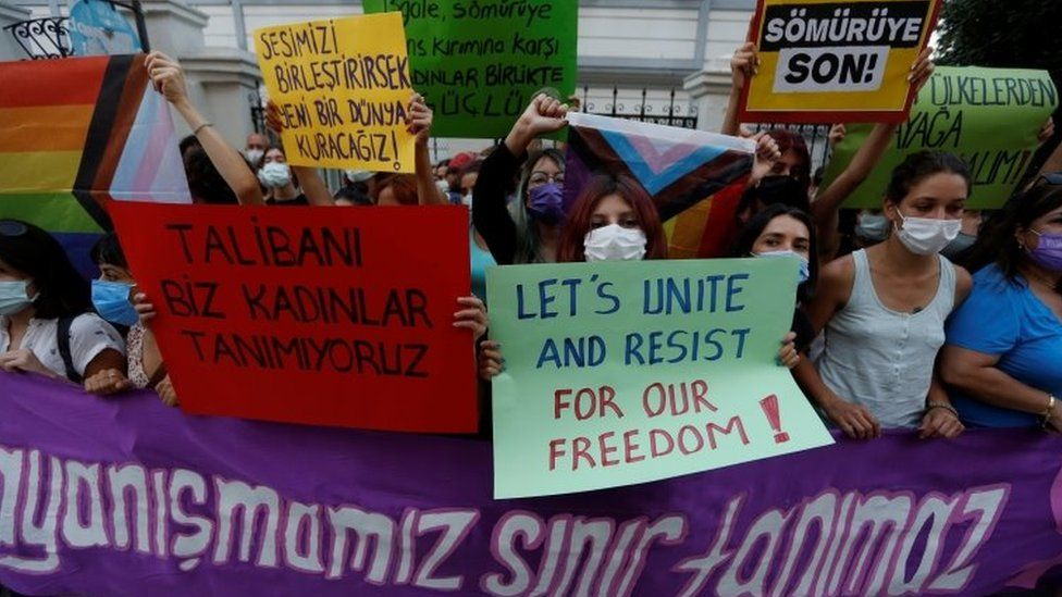 """Activists hold placards saying """"Our solidarity no boundaries"""" and """"We, women don't recognise the Taliban"""" at a protest following the Taliban's takeover of Afghanistan, in Istanbul, Turkey (20 August 2021)"""