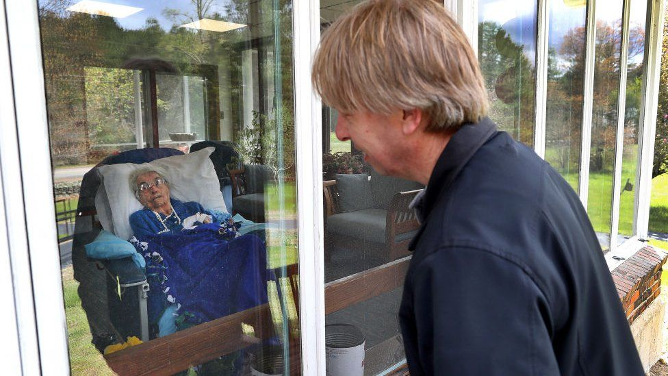 Family member looks through window at woman in nursing home