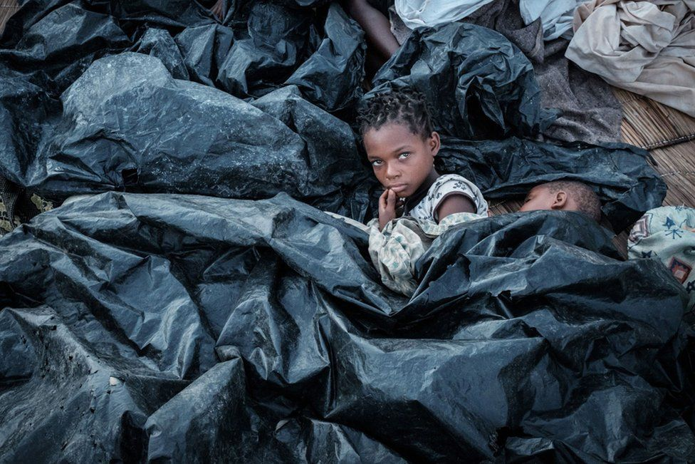 Enia Joaquin Luis, 11, wakes up beside her sister Luisa, 6, under plastic sheets to protect themselves from rain at a shelter in Buzi, Mozambique, following Cyclone Idai in March.