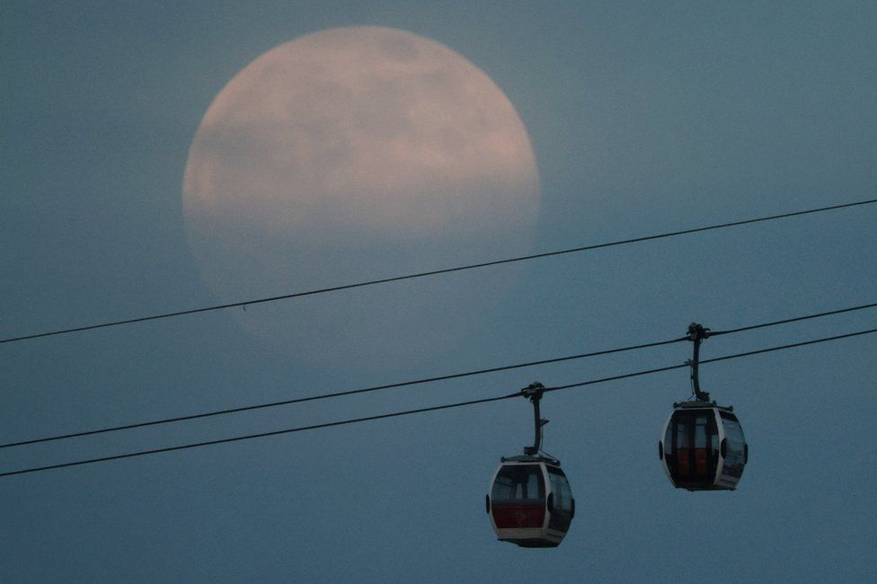 The supermoon rises in the sky above the Emirates Air Line cable car in London
