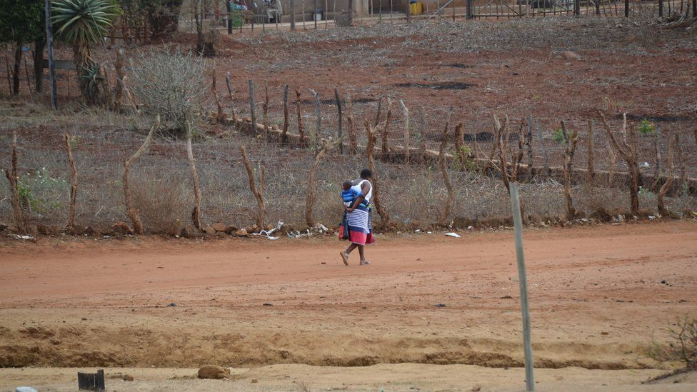 A woman walks through a village with a baby on her back