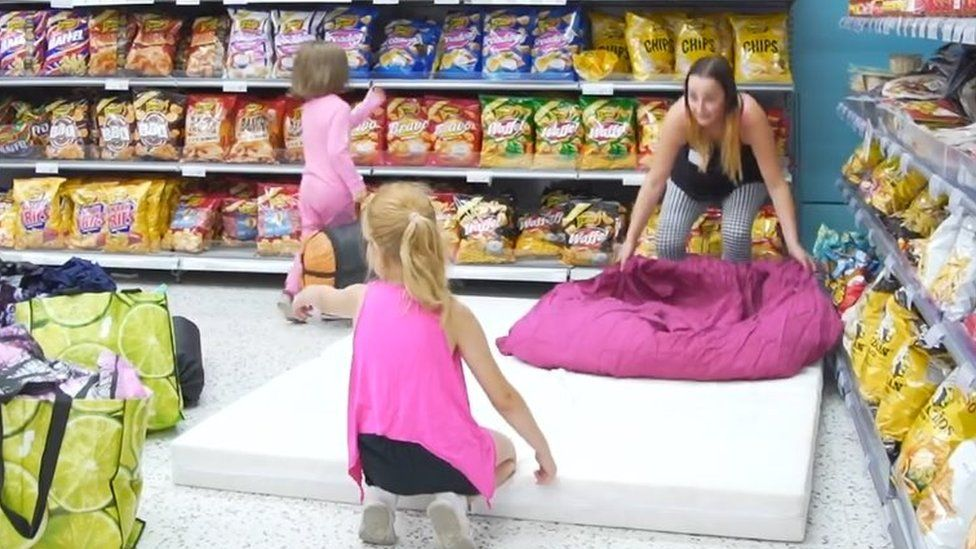 A woman and two children place a mattress near the crisps aisle