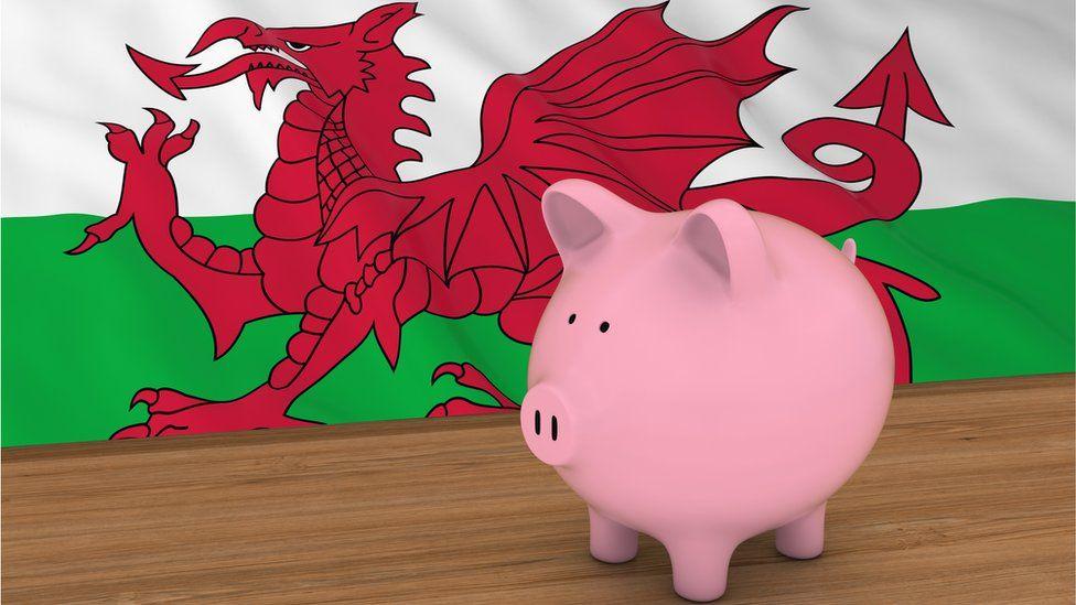 Piggybank in front of Welsh Flag