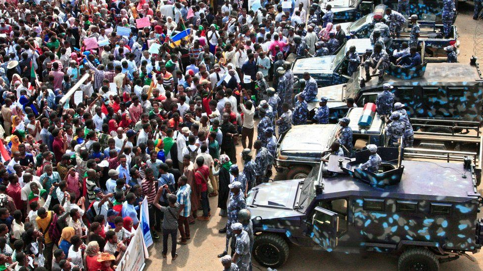 People rally before security forces' vehicles at a mass demonstration near the presidential palace in Sudan's capital Khartoum
