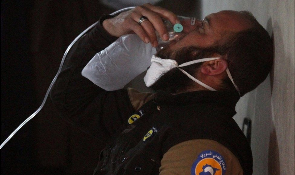 A rescuer breathes through an oxygen mask after the attack on Khan Sheikhoun