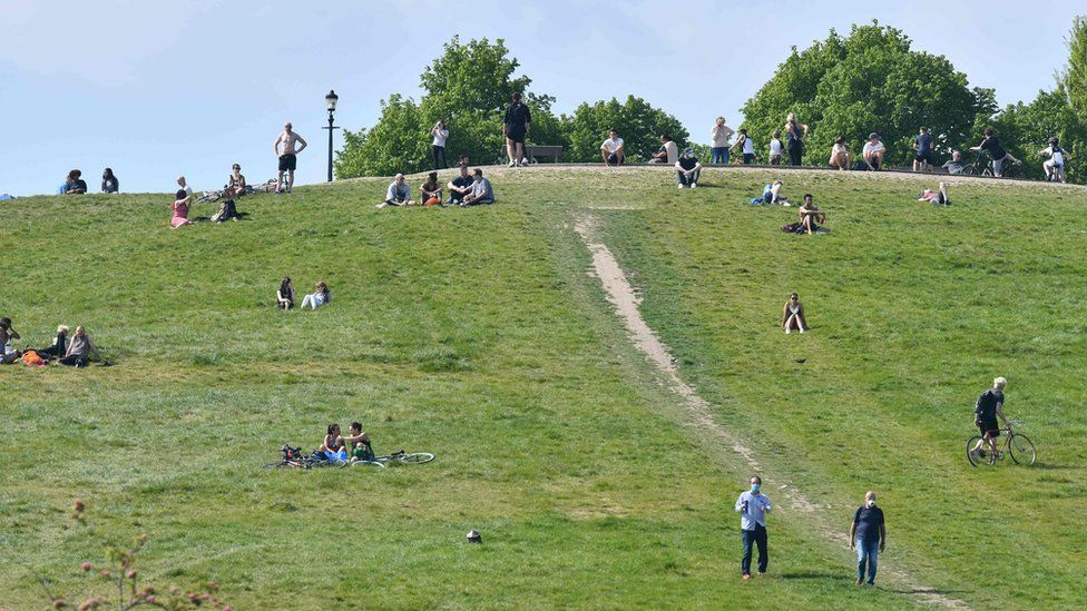 People are dotted about relaxing in the sunshine on Primrose Hill in London on May 7, 2020 as life continues in Britain under a nationwise lockdown to slow the spread of the novel coronavirus.