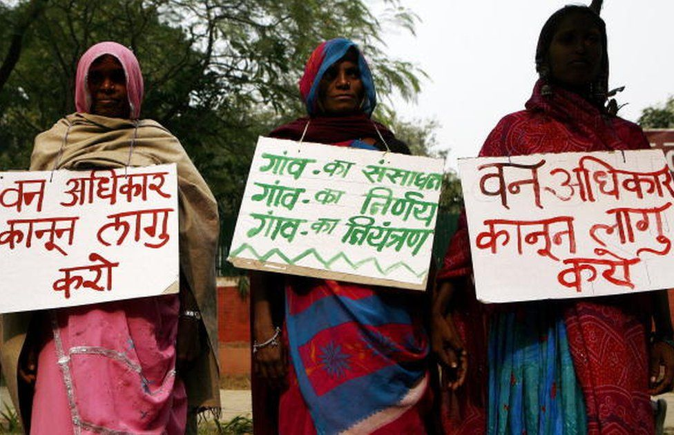 Indian tribal women hold placards as they form a human chain during a protest against the government in New Delhi, 30 November 2007.