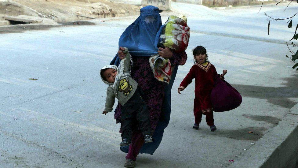 Afghan woman and her children run for cover in Jalalabad on 24 January 2018