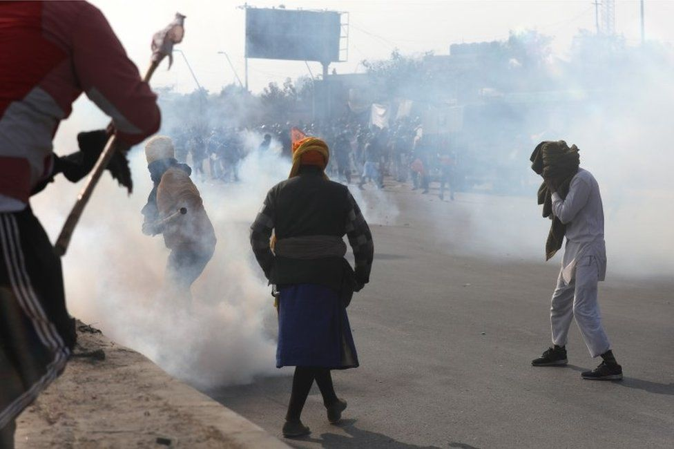 """Police use tear gas against farmers during a """"parallel parade"""" on tractors and trolleys amid their ongoing protest against the new agricultural laws, on the outskirts of New Delhi, India, 26 January 2021."""