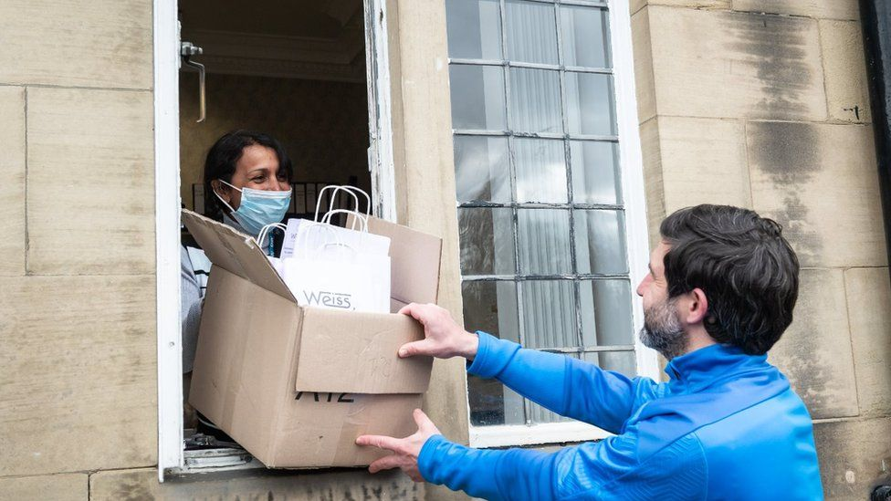 Man passes box to woman through window