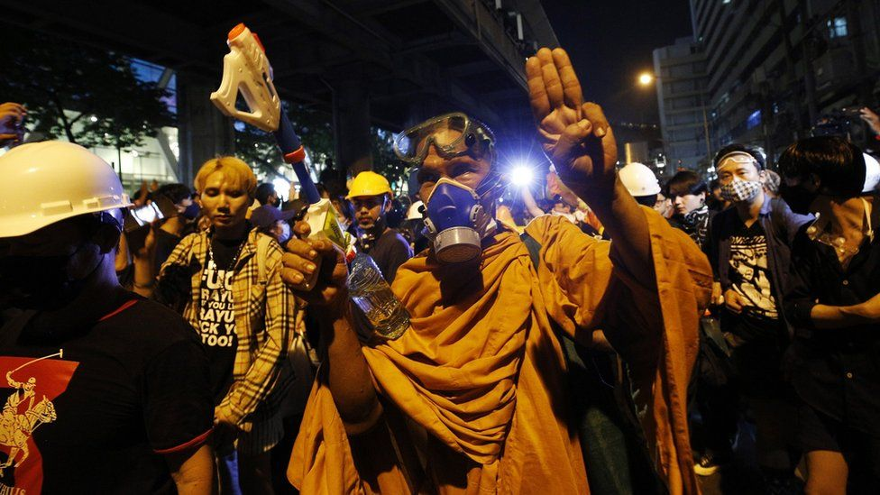 A monk wearing a gas masks flashes the three singer salute walk among pro-democracy protesters