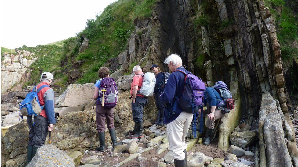 People looking for fossils in Burnmouth in Scotland