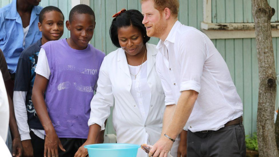 Prince Harry guts a fish during his visit to Sir McChesney George High School.