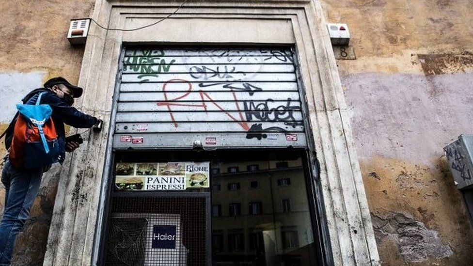 A man closes a sandwich bar in Rome, Italy. Photo: 12 March 2021