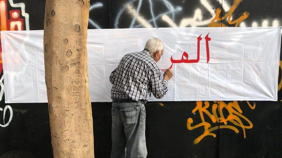 Old man writes anti-sectarian slogans on a wall in Beirut
