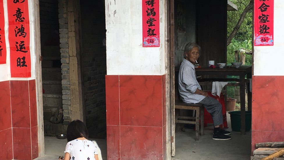A young girl playing whilst an older lady stares out in the distance