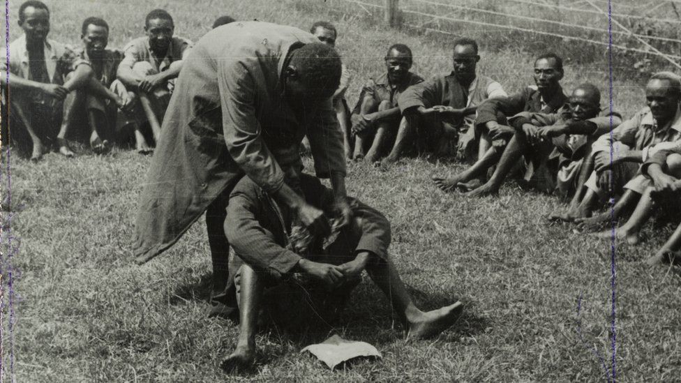 Government de-oathing ceremony, 1953 - A Mau Mau detainee sitting in the centre of a circle of men in a fenced compound is purified of the Mau Mau oath.