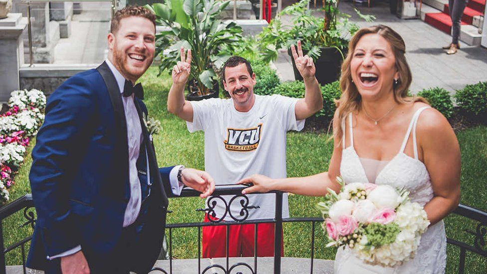 Adam Sandler dressed in running gear poses with a bride and groom at their wedding