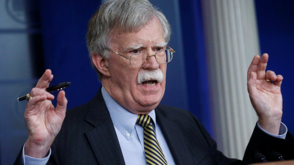 John Bolton raises his hands in the air as he speaks from a podium