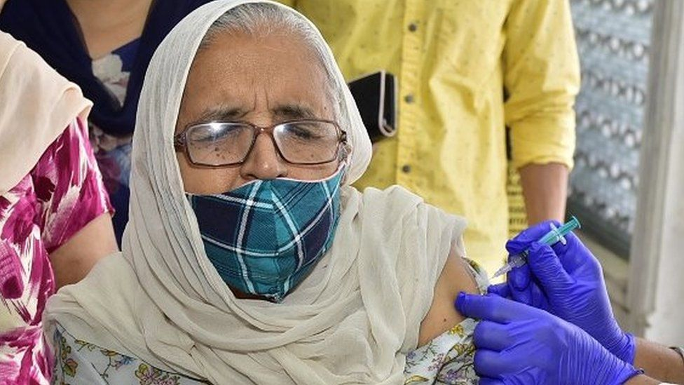 A medical worker administers a dose of vaccine to a beneficiary at a vaccination camp.