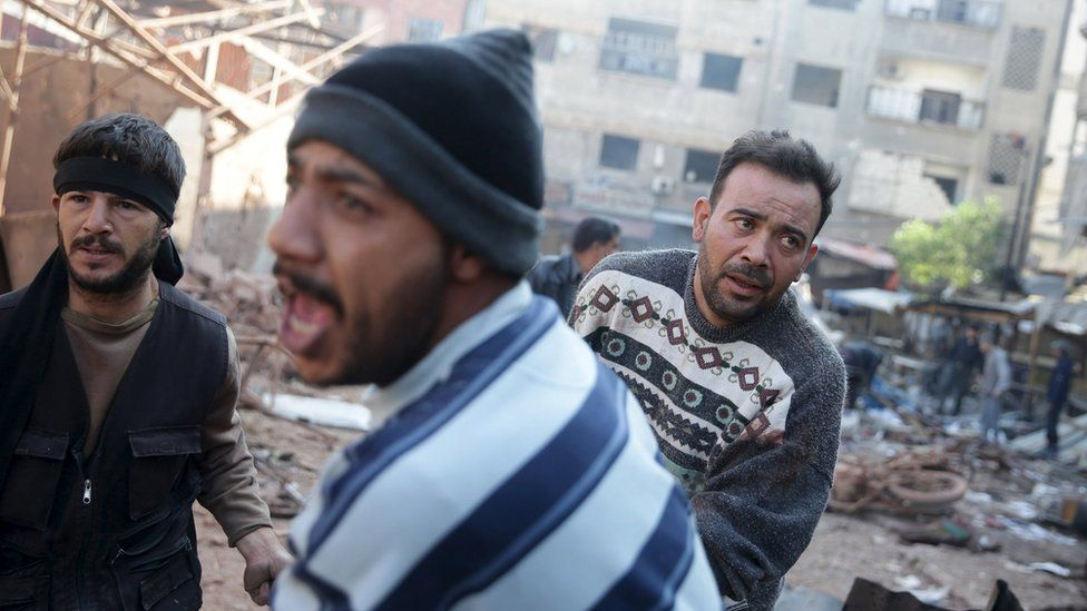 Men react as they carry the remains of dead people at a damaged site hit by missiles fired by Syrian government forces on a busy marketplace in the Douma neighbourhood of Damascus, Syria October 30, 2015.
