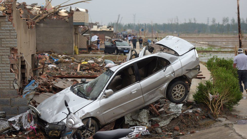 """Residents walk in the rubble of destroyed houses after a tornado in Funing, in Yancheng, in China""""s Jiangsu province on June 24, 2016"""