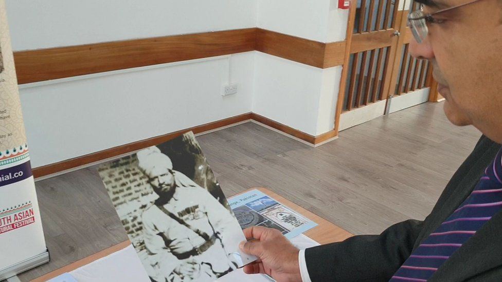 Dr Irfan Malik looking on at picture of his great grandfather.