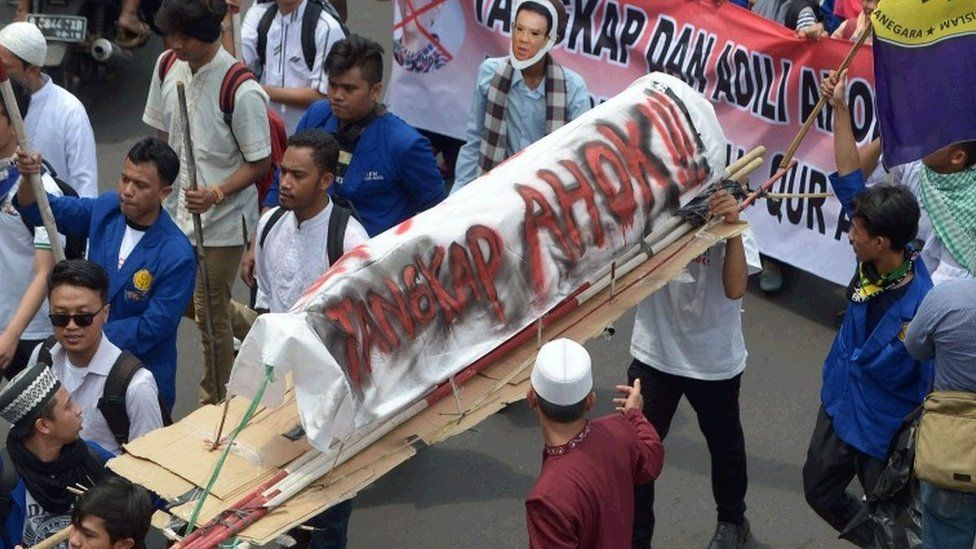 """Indonesian Muslim students carry a mock coffin that reads: """"Arrest Ahok"""", as Muslims march towards the presidential palace during a protest against Jakarta governor Basuki Tjahaja Purnama also known as Ahok over an alleged blasphemy in Jakarta on November 4, 2016."""