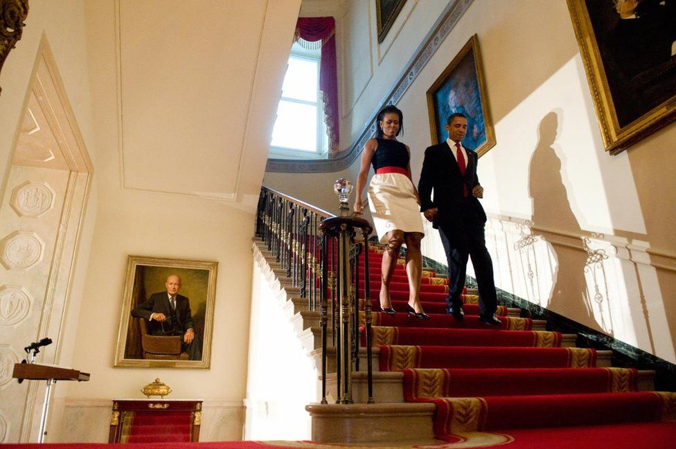 US President Barack Obama and First Lady Michelle Obama walk down from the residence into the Grand Foyer of the White House in Washington, DC, July 27, 2009