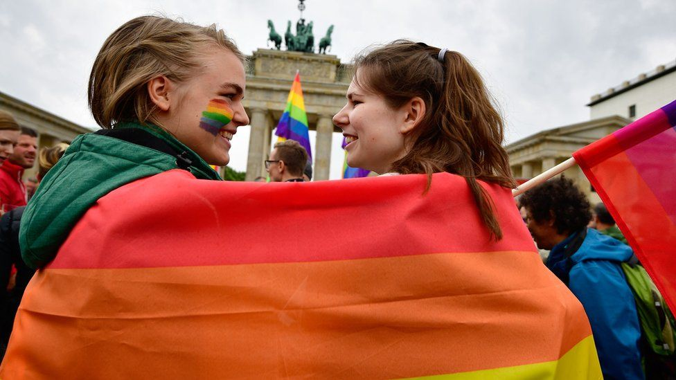 Two women wrapped in a rainbow flag at a rally in Germany