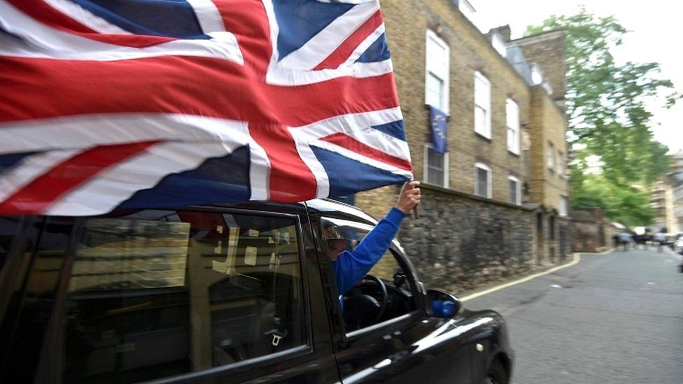 Taxi driver holding Union Jack flag