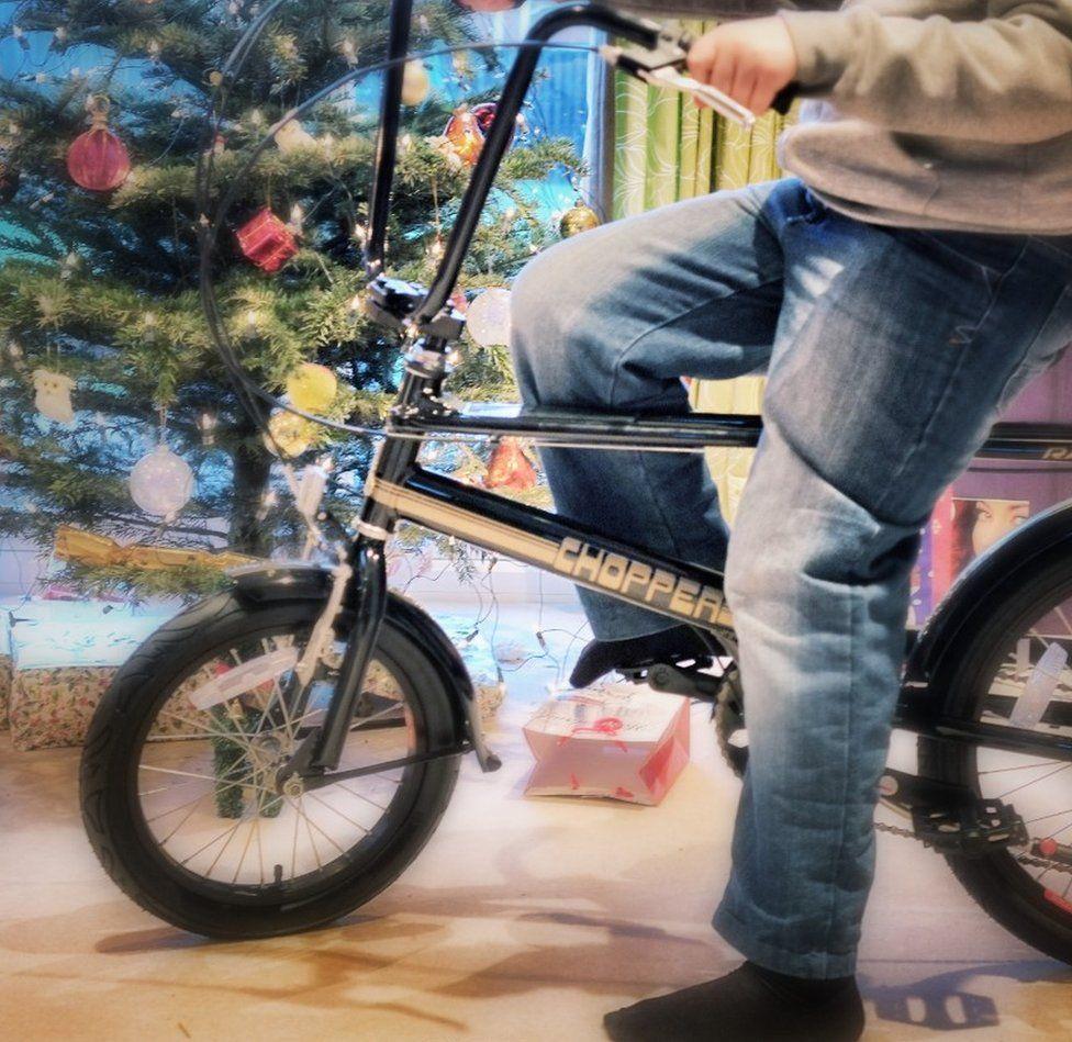 Boy sits on a new bike on Christmas day in Glasgow, Scotland