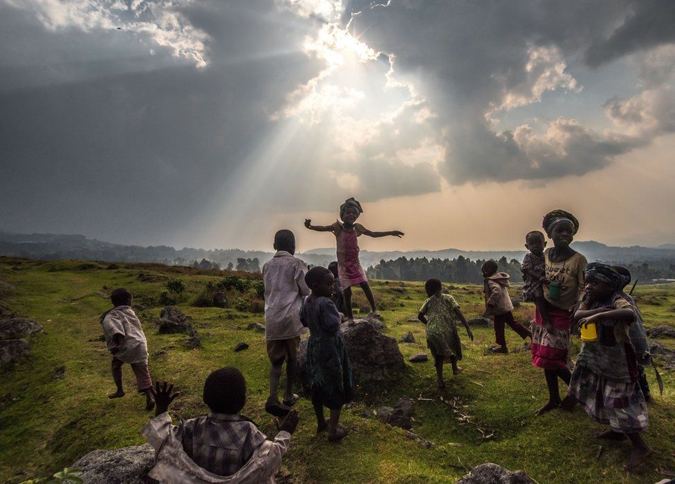 children in a green expanse, one jumping up and down on a rock, as the sun breaks through a cloud