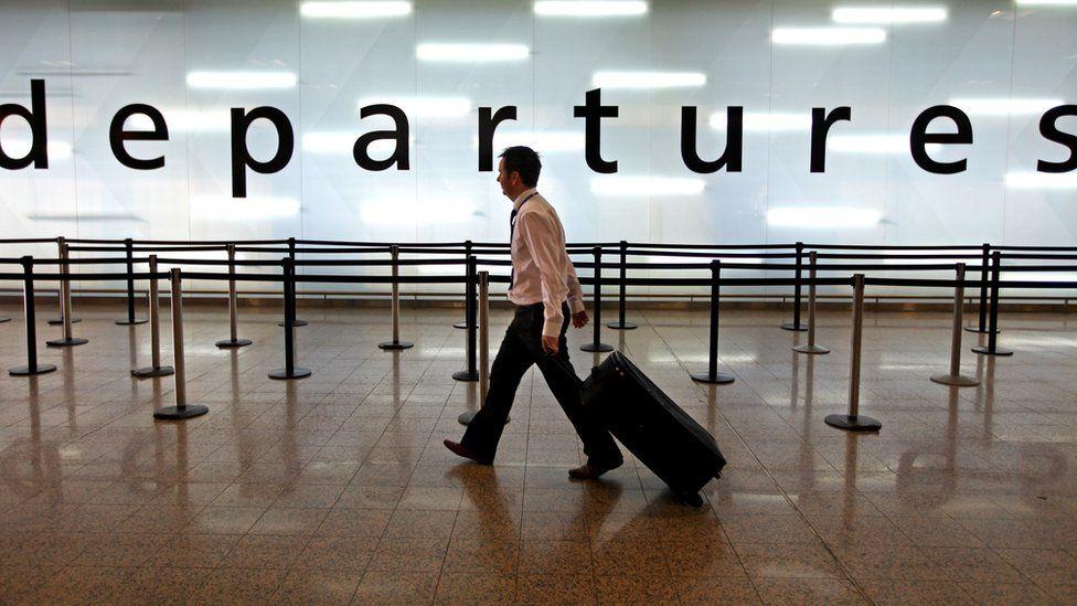 Man walking through airport departures