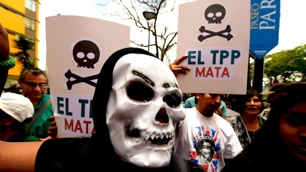 Protesters hold placards against the Trans-Pacific Partnership (TPP) during a rally on the sidelines of the Asia-Pacific Economic Cooperation (APEC) Summit in Lima
