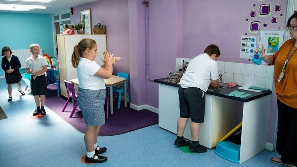 Pupils queue to wash their hands