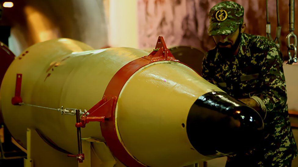 Member of the Revolutionary Guards next to a missile launcher in an underground tunnel at an undisclosed location in Iran