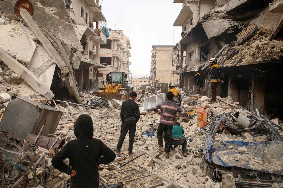 Rescue workers clear debris from the site of an air strike in Ariha, in Idlib province, Syria (30 January 2020)